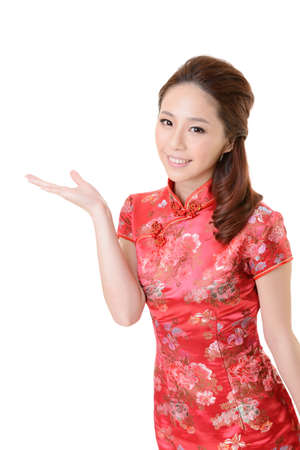 introduce: Smiling Chinese woman dress traditional cheongsam and introduce on white background. Stock Photo