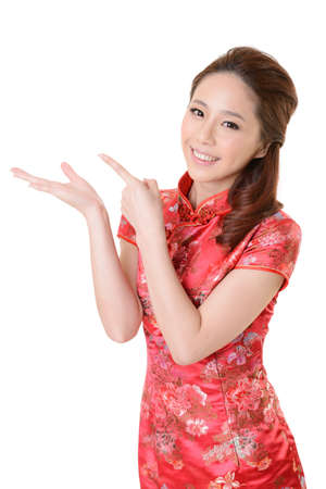 cheongsam: Smiling Chinese woman dress traditional cheongsam and introduce on white background. Stock Photo