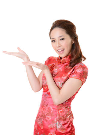 Smiling Chinese woman dress traditional cheongsam and introduce on white background. Stock Photo