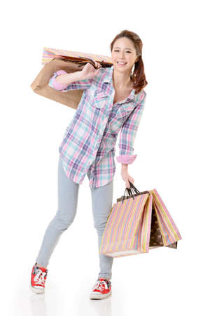 Happy shopping woman of Asian holding bags against white background. photo