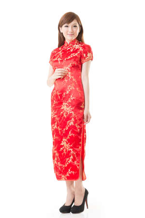 Smiling Chinese woman dress traditional cheongsam at New Year, studio shot isolated on white background. Stock Photo
