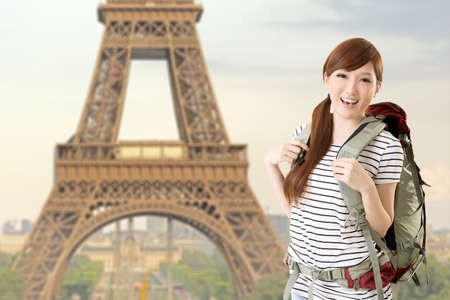 Happy smiling Asian woman travel and look at you in front of famous landmark, Eiffel tower in Paris, France. photo