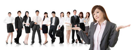 shrugs: Helpless young business woman shrugs her shoulders in front of her team on white background.