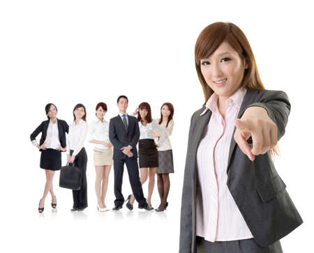 We want you, Asian business woman point at you in front of her team isolated on white background. photo