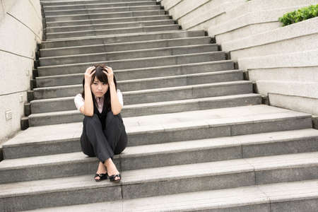 stressed business woman: Sad business woman feel worried and stressed in outside of modern city. Stock Photo