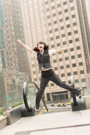 Business woman jump and excited in outside of modern city. photo