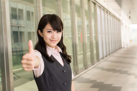 Business woman give you an excellent sign, closeup portrait in outside of modern city. Stock Photo - 18572601