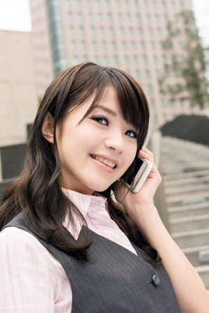 Business woman of Asian talk on cellphone, closeup portrait in urban. photo