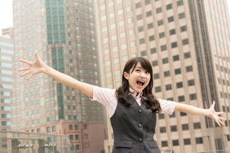 Exciting business woman raised hand in outside of city. photo