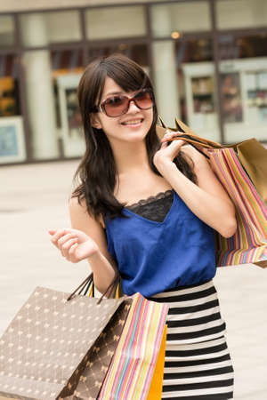 Fashion lady of Asian holding shopping bags in modern city. photo