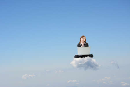 cloud computer: Business woman sit on cloud and use laptop over sky.