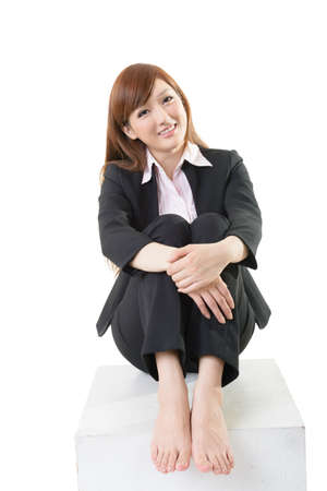 asian working woman: Studio shot of attractive Asian business woman sit on white box, element for designer for sit and rest concept.