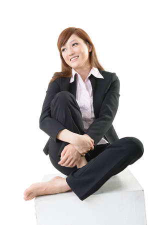 Studio shot of attractive Asian business woman sit on white box, element for designer for sit and rest concept. photo