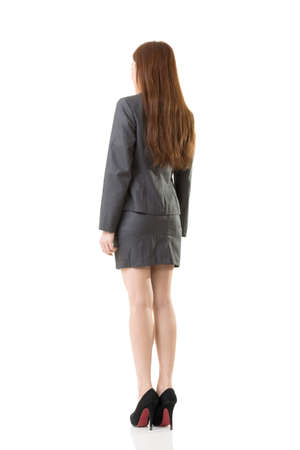 Full length person of Asian business woman wear skirt suit, rear view portrait isolated on white background.
