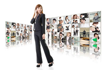Business woman talk on cellphone in front of video wall. Business conferencing and global communications concept. photo