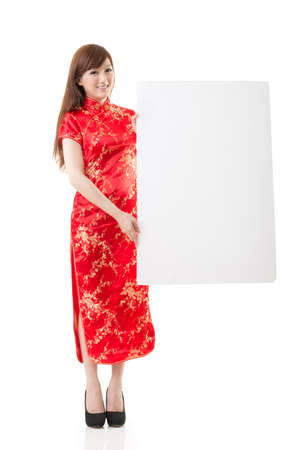 qipao: Attractive Chinese woman dress traditional cheongsam and hold blank board, studio shot portrait on white background.