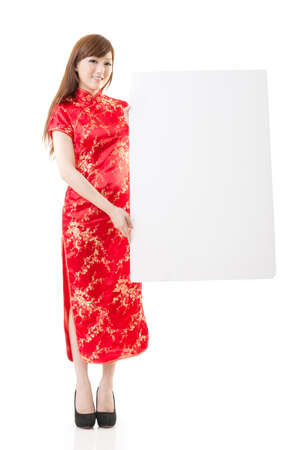 instruction sheet: Attractive Chinese woman dress traditional cheongsam and hold blank board, studio shot portrait on white background.