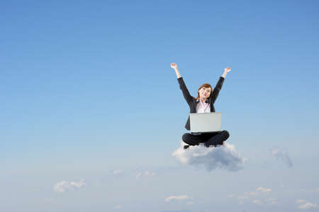 Business woman sit on cloud and use laptop over sky. photo