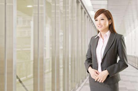 Vertrouwen Aziatische zakenvrouw staan voor kantoorgebouwen.