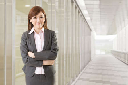 Confident Asian business woman stand in front of office buildings. photo
