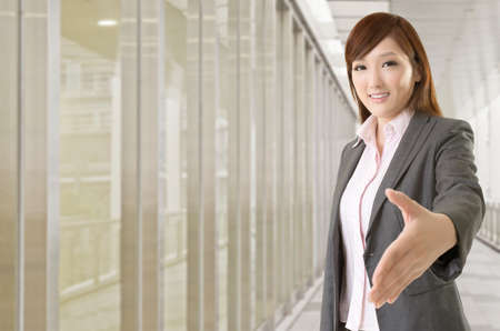 Confident business executive woman of Asian make a handshake with you, half length closeup portrait on white background. photo