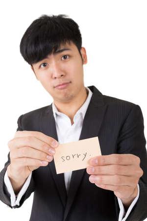 Asian businessman holding a card written on sorry, closeup portrait.