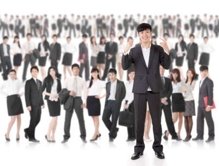 Young cheerful businessman of Asian point at himself and stand in front of huge group business people on white background. Concept of cheerful, confident, successful and volunteer idea. photo