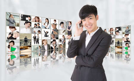 Young businessman talk on phone and stand in front of tv screen wall showing pictures of business concept by Asian business people. Concepts about business, communication, teamwork or social network. photo