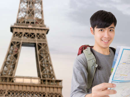 Asian young traveler of man hold map and look at you in front of the famous landmark, Eiffel Tower, France. photo