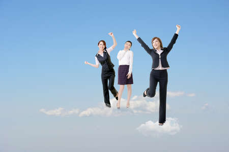 Cheerful three Asian business women stand on clouds and raise their arms feel freedom and exciting over blue sky.