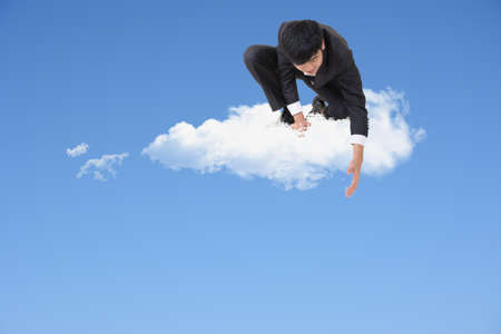 Asian businessman sit on cloud and reach out his hand for help you over blue sky. photo