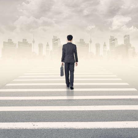 dreams of city: Single businessman walk cross the road into urban.
