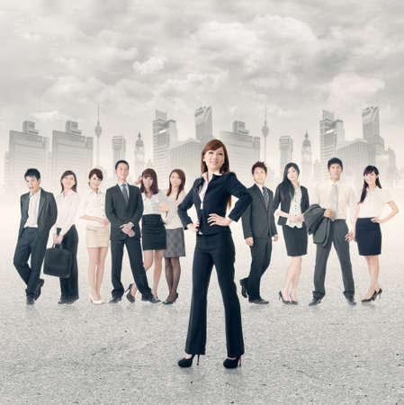 Confident business manager with her business team stand on road in modern city. photo