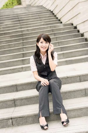 Asian business woman sit on stair and talk on cellphone in daytime urban. photo