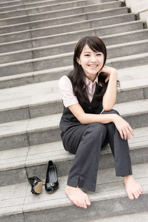 Happy smile business woman rest and take off her shoe in outside of urban. photo