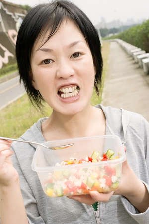 person appetizer: Mature Asian woman eat salad in outdoor park in daytime.