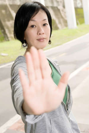 reject: Sport mature woman give you a gesture sign of , closeup portrait in outdoor park in city. Stock Photo