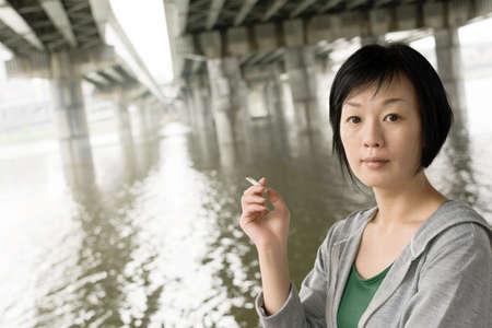 Closeup portrait of mature Asian woman smoking under bridge at city in daytime. photo