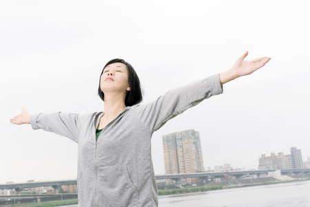 Ältere asiatische Frau fühle mich frei und offenen Armen in der Tageszeit an der Stadt.