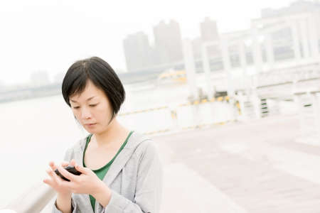Mature Asian woman talk on cellphone in daytime. Stock Photo - 19628579
