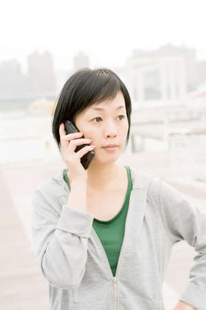 Mature Asian woman talk on cellphone in daytime. photo
