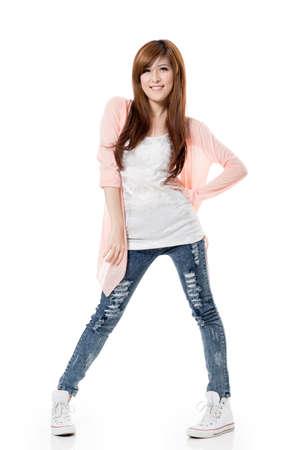 excitacion: Muchacha sonriente feliz de Asia permanente y posando sobre fondo blanco de estudio.