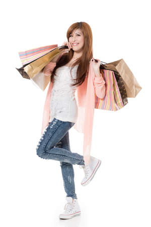 excitation: Cheerful shopping woman of Asian holding bags on white studio background.