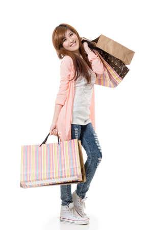 excitacion: Alegre mujer de compras de las bolsas asi�ticas que se sostienen en el fondo blanco del estudio.