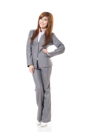 business woman standing: Attractive Asian business woman standing against studio white background, full length portrait.