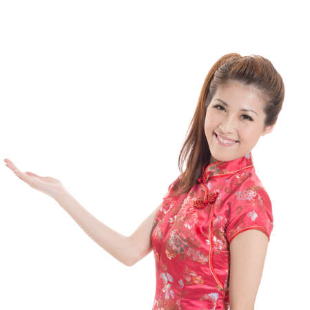 qipao: Smiling Chinese woman dress traditional cheongsam and introduce on white background. Stock Photo