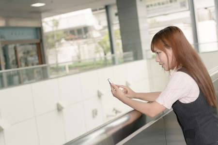 Asian business woman use her cell phone in modern city, Taipei, Taiwan, Asia. photo