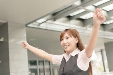 Cheerful Asian business woman raising arms, closeup portrait in outside , Taipei, Taiwan, Asia. photo