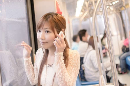 Asian beauty in MRT carriages use her cellphone, Taipei, Taiwan. photo