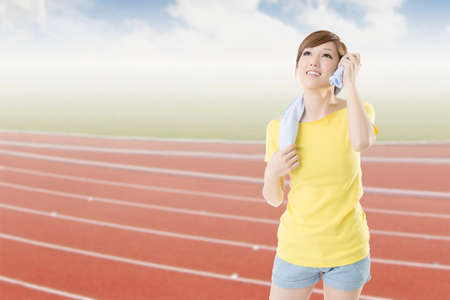 Smiling athletic woman take a rest after training, closeup portrait in outdoor sport field. photo